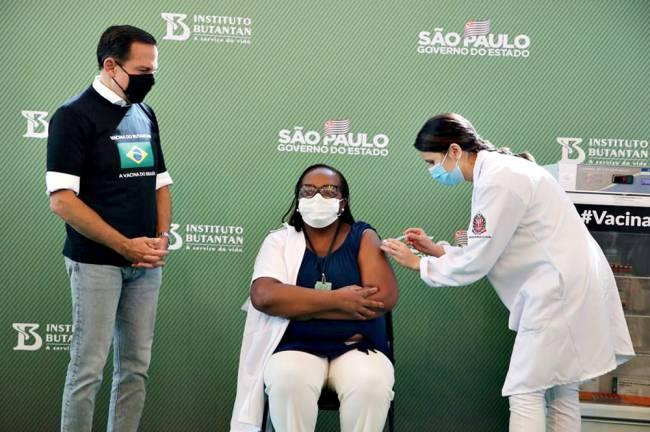 A enfermeira Mônica Calazans tomando a primeira dose da vacina CoronaVac, ao lado de João Dória, governador de São Paulo
