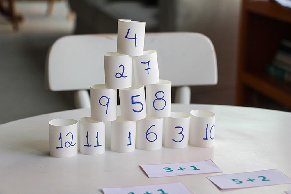 Pirâmide feita com tiras de papel com números escritos. Na mesa, as operações correspondentes a cada linha da pirâmide.