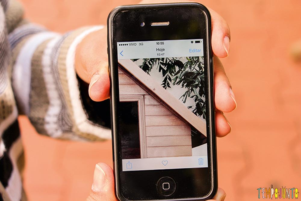 Foto de um celular mostrando outra foto, de um ambiente externo de uma casa