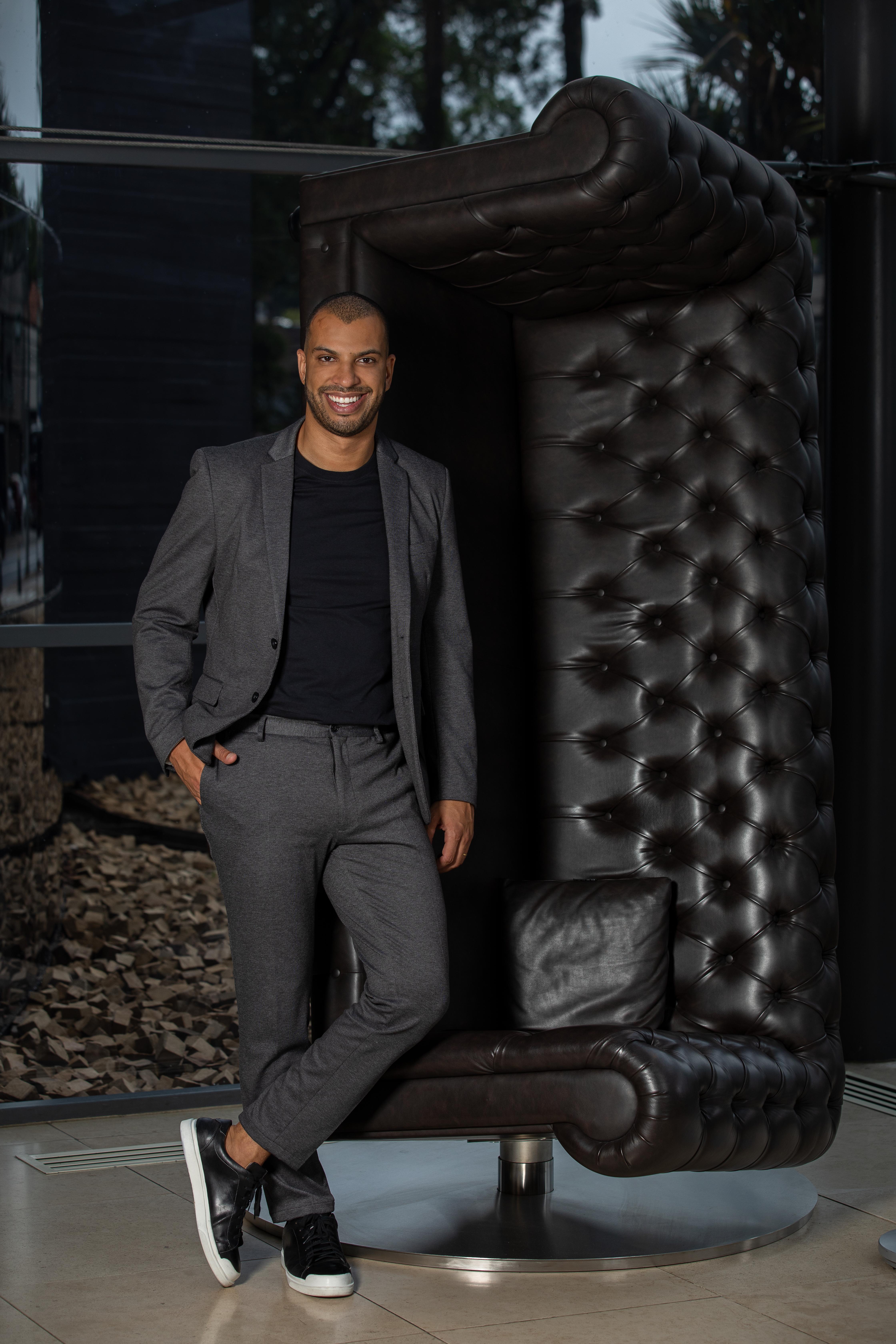 Wellington Melo, do Unique, posa de pé ao lado de sofá de couro preto erguido de pé como escultura. Veste terno cinza com camiseta preta.