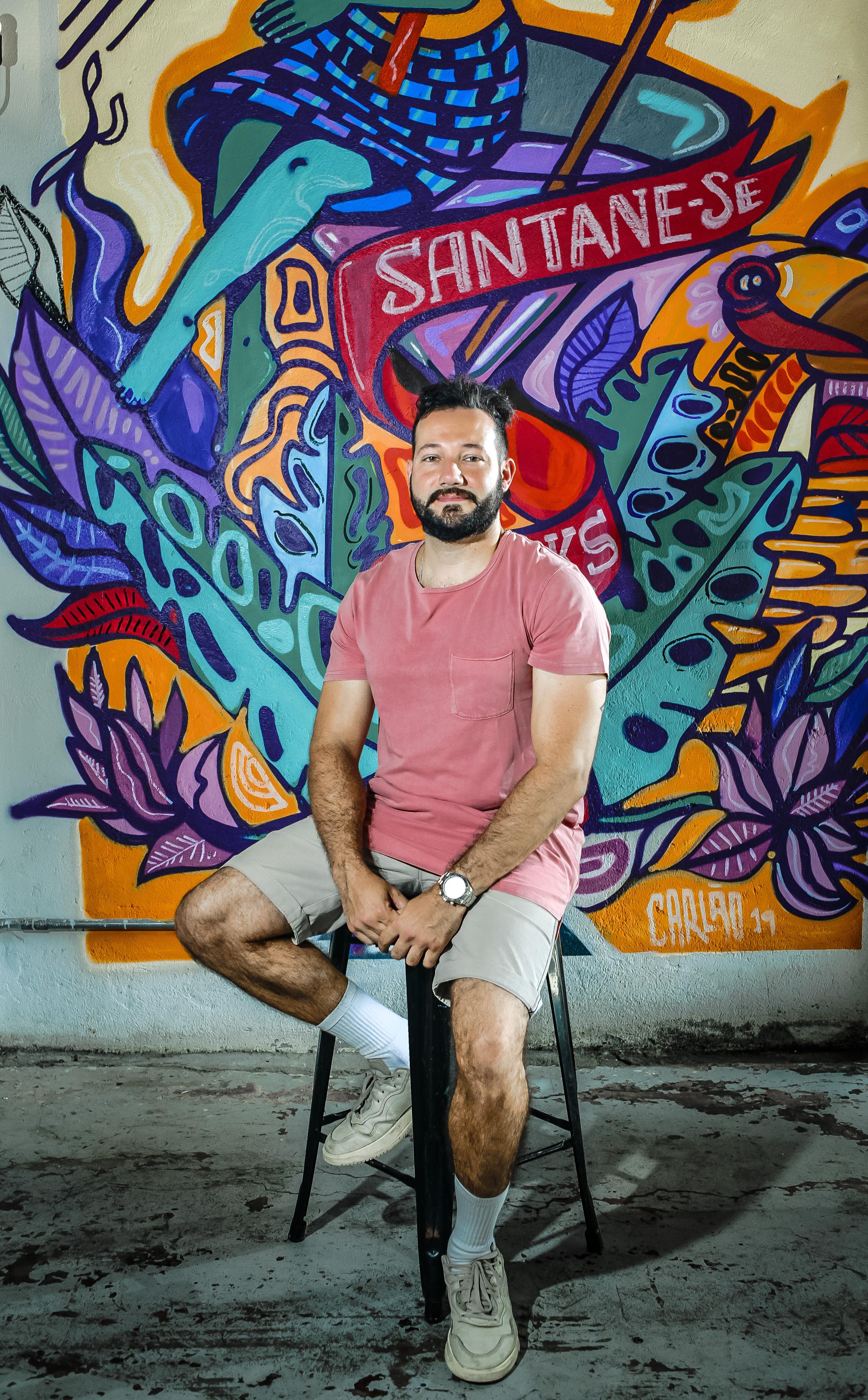 Imagem mostra dono do Degrau Bar, Pedro Fargetti, sentando em banqueta com grafite colorido ao fundo