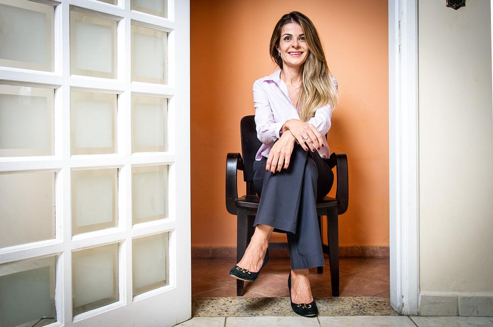 Denise sentada em um banco de escritório