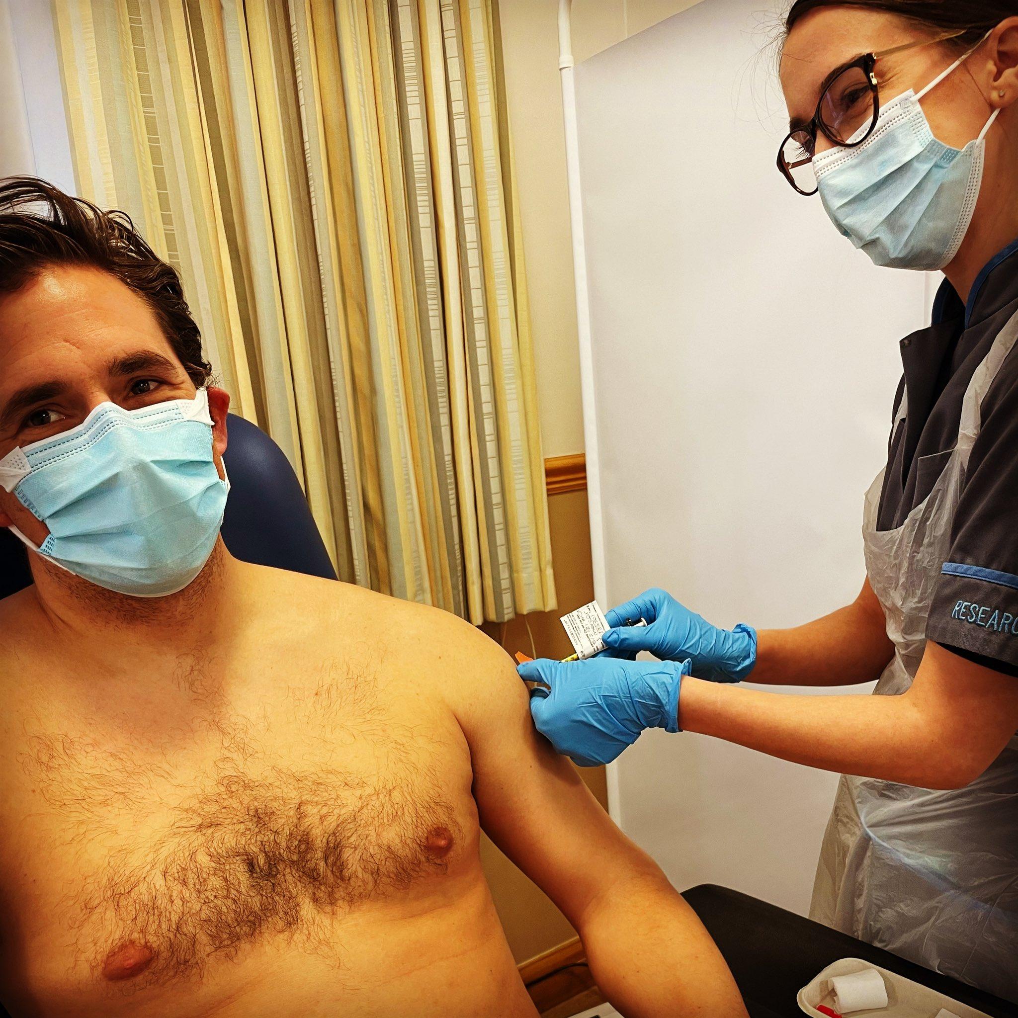 Imagem mostra o político britânico Johhny Mercer sem camisa tomando vacina contra a Covid-19
