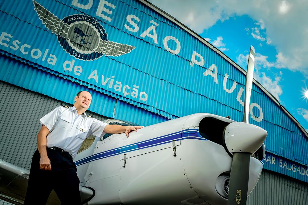 Fernando apoiado em um avião, à frente do Aeroclube