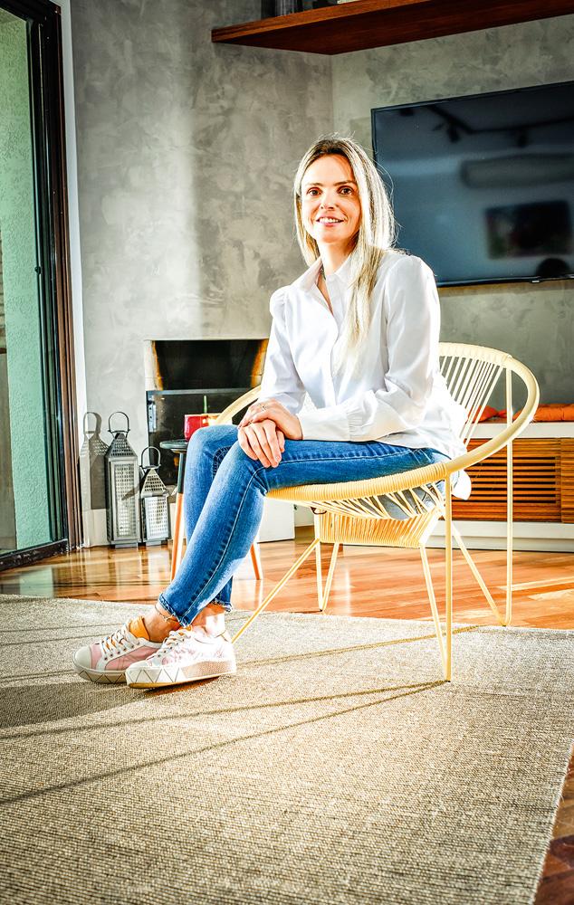 Flavia Janini sentada em sua sala