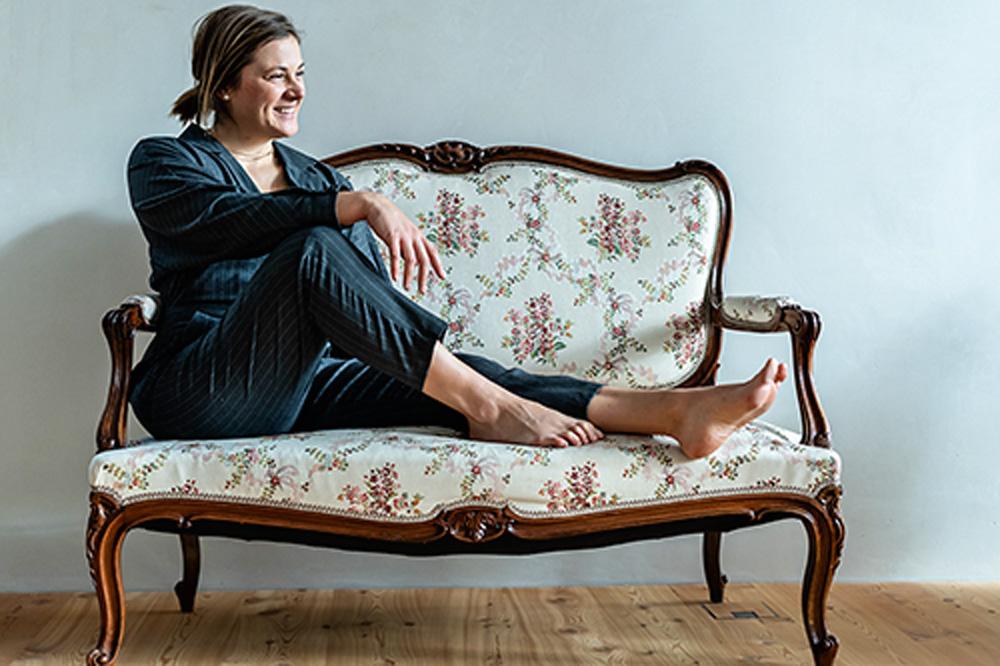 Artista Kalina Juzwiak posa para foto sentada em um sofá