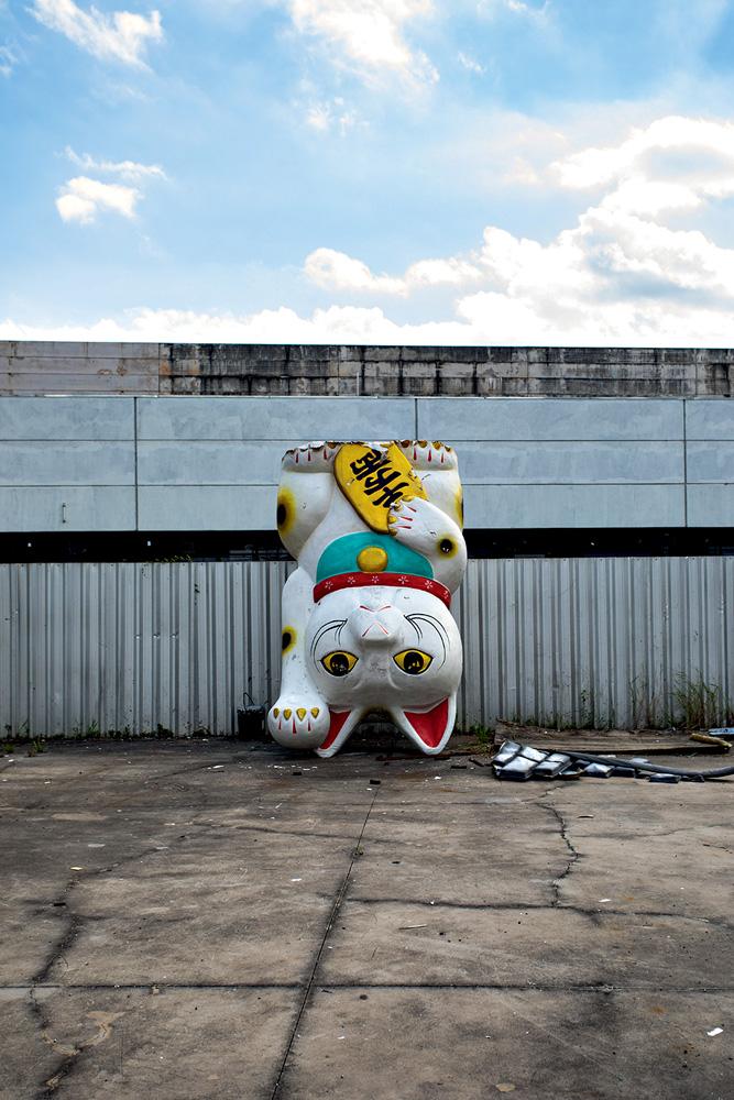 Obra de gato feita para um carro alegórico de ponta cabeça, encostado na parede