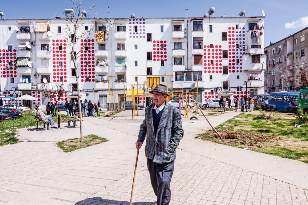 Um idoso caminhando nas ruas de Tirana
