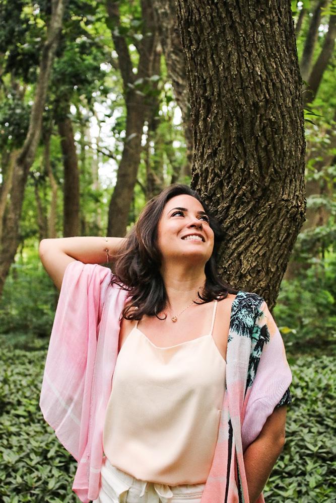 Luciana em uma área aberta, com plantas, e rindo