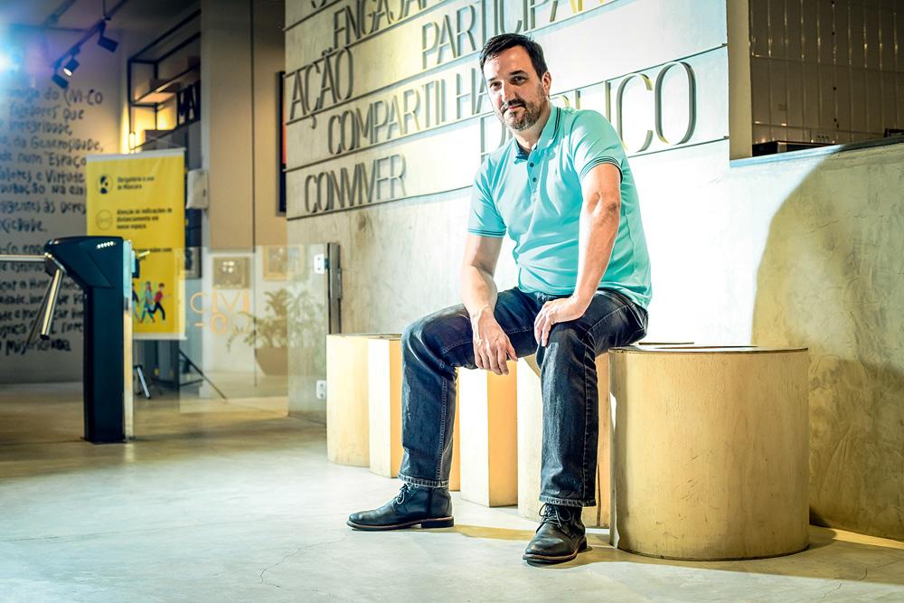 Marcelo de Vita Grecco, sentado em um banco de madeira cilíndrico