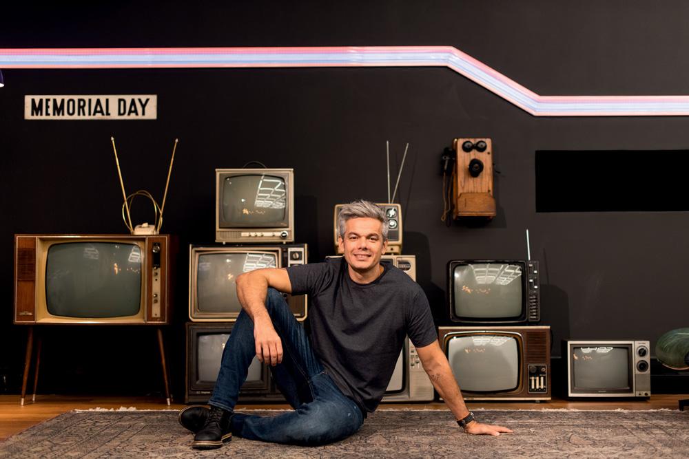 Otaviano Costa deitado com um cenário cheio de televisões ao fundo