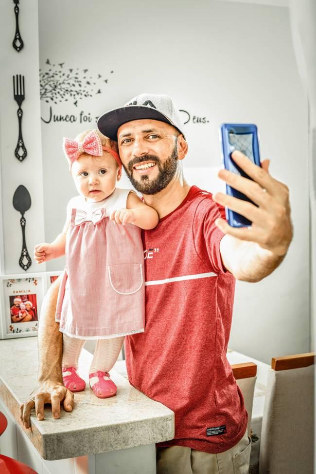 Imagem mostra o casal Renato Celestino e filha Lívia posando para foto encenando uma selfie