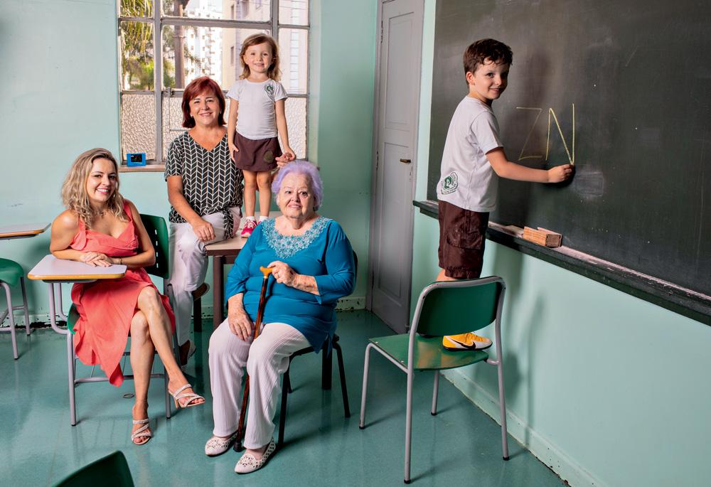 Família em uma sala de aula, com um menino rabiscando a lousa