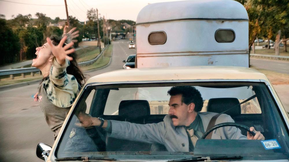Borat dentro do carro, segurando a filha que está saindo pela janela