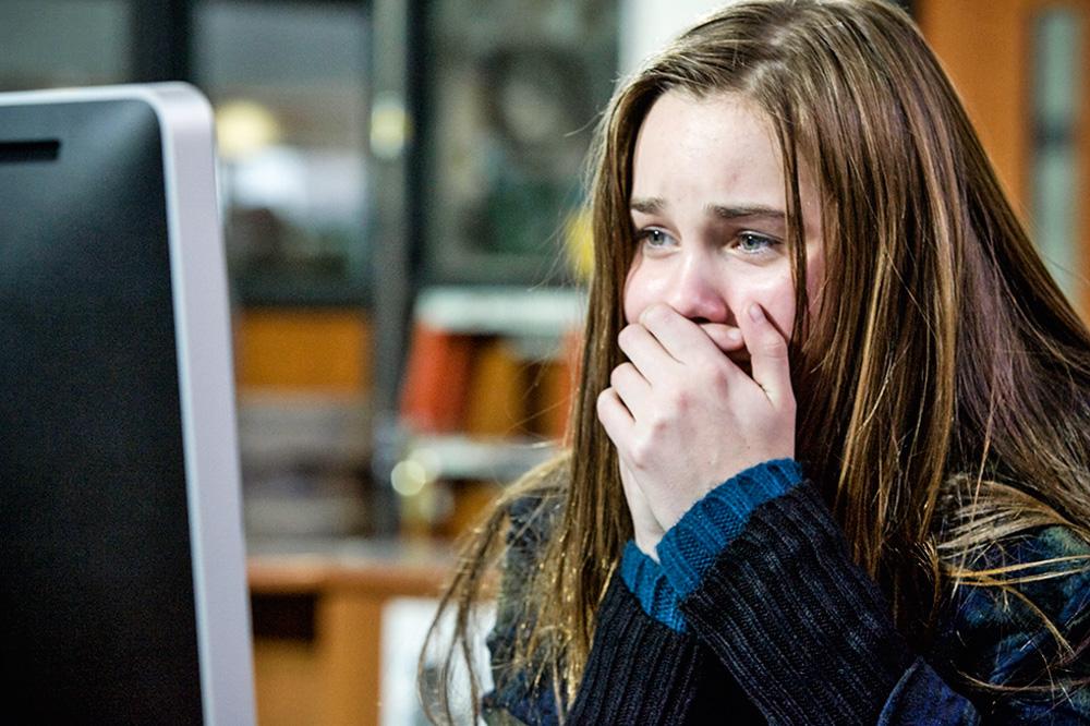 menina chorando na frente do computador