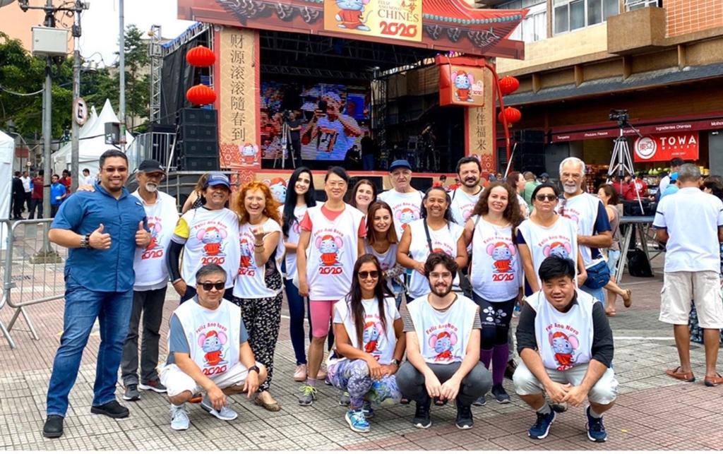 grupo de pessoas de colete branco posando para a foto na frente de um palco