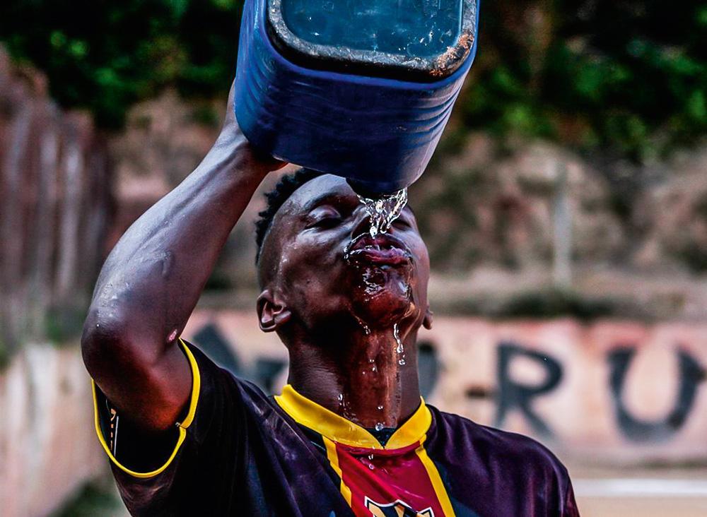 Jogador tomando água com um garrafão de água azul