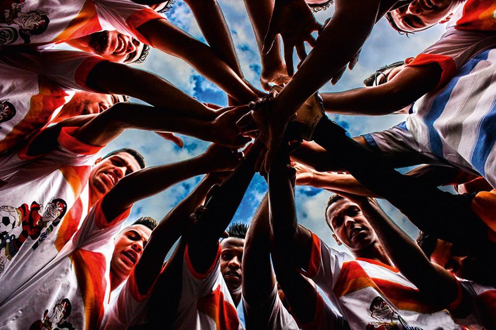 Time em círculo, com todos colocando uma mão no meio juntos