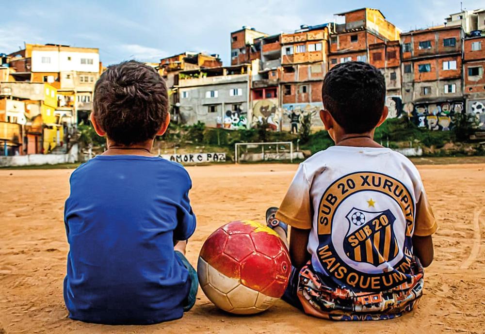 Duas crianças sentadas em um campo de terrão, com uma bola vermelha entre elas. A visão é das costas dela, e ao fundo elas tão observando um gol vazio