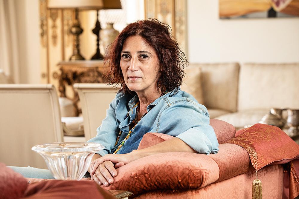 Grace Cury sentada no sofá virada para a foto com expressão séria