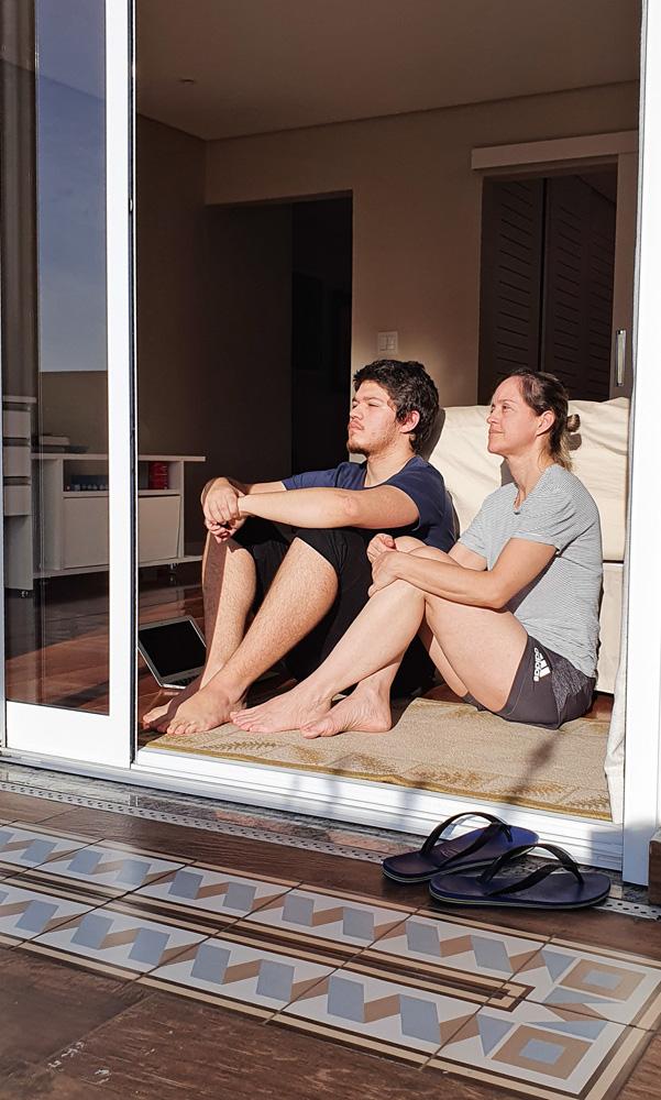 guilherme e a mãe sentados no chão olhando para o horizonte