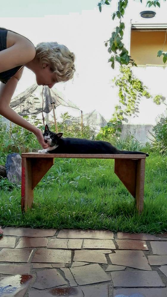 Paloma Cassari e acariciando Ártemis, sua gatinha