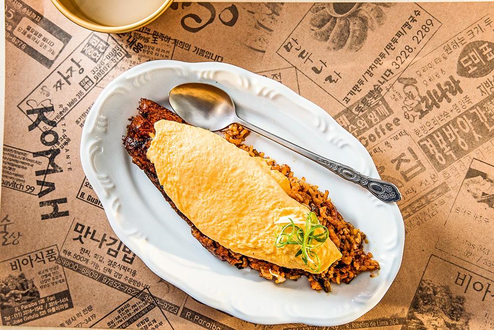 Komah: arroz salteado com acelga fermentada e picante, coberta por omelete cremosa
