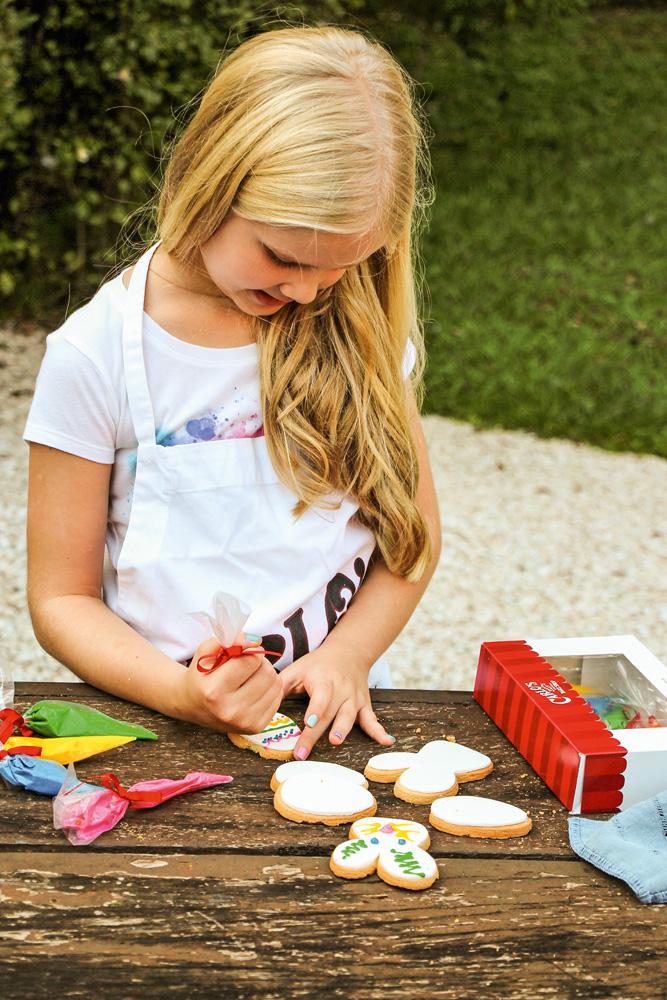 Menina loira decora biscoitos amanteigados de páscoa