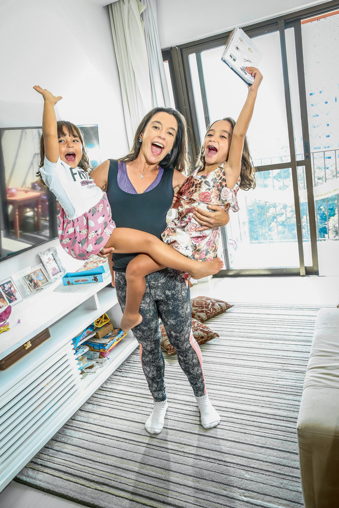 Mãe segurando as duas filhas no colo. As duas crianças estão com as mãos para cima e estão todas na foto sorrindo