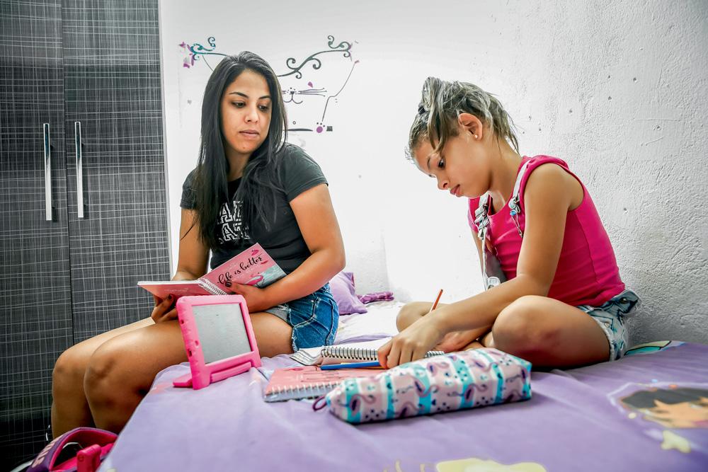 Mãe olhando para a filha, que está fazendo uma lição em cima da cama