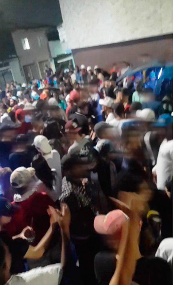 Baile funk com a rua completamente lotada de pessoas, todas sem máscaras e apertadas