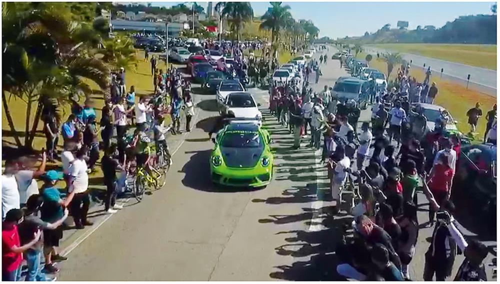 Aglomeração de pessoas assistindo a uma corrida de racha