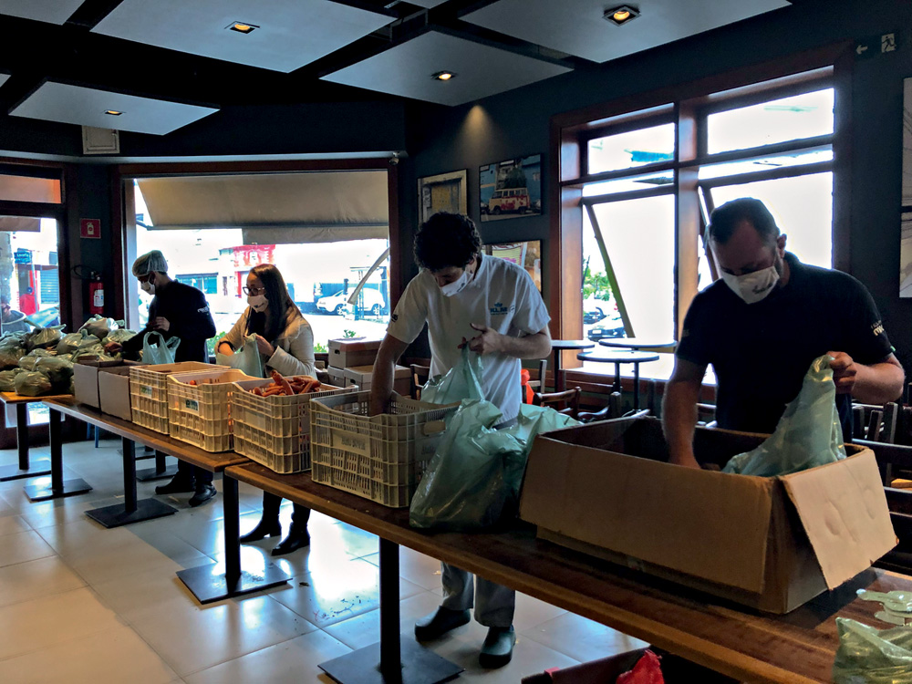 Funcionários, de máscara, montando as marmitas no salão dos restaurante