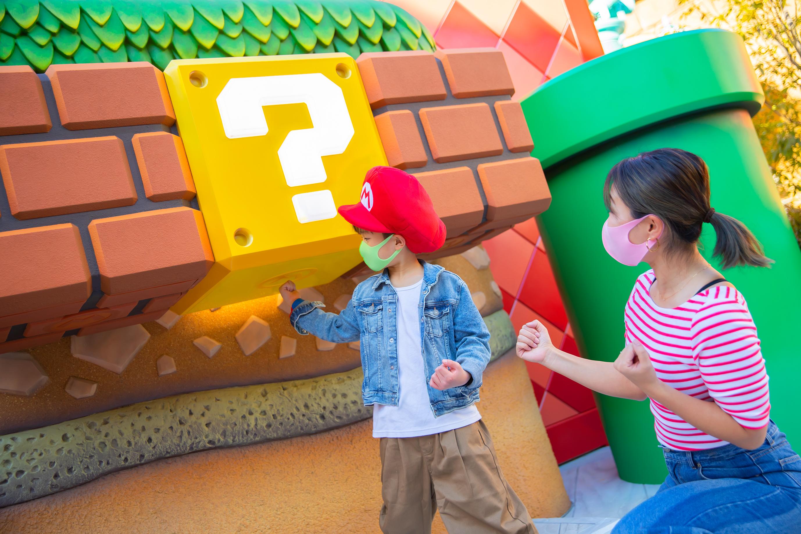 Criança de máscara batendo no bloco do Mario World