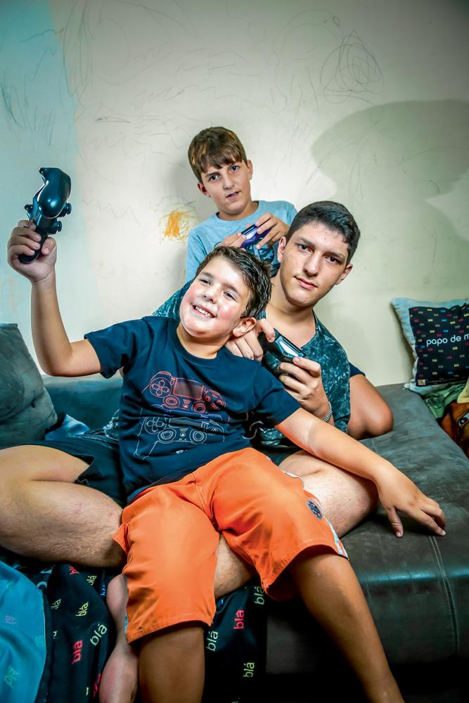 Os três irmãos, em um sofá, cada um com um controle diferente do videogame