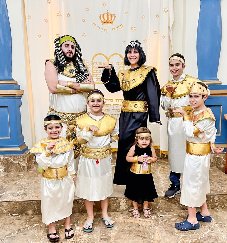 Pedro, sua mulher e os filhos vestidos para a festa de Purim posando para a foto