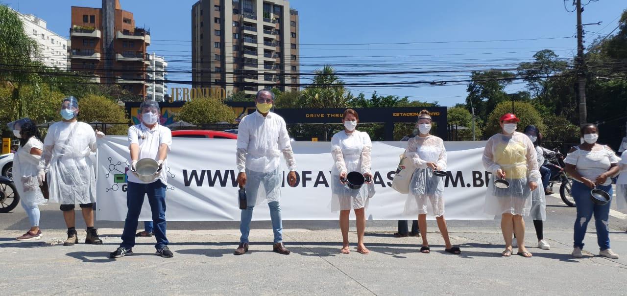 manifestantes posando para a faixa segurando um cartaz