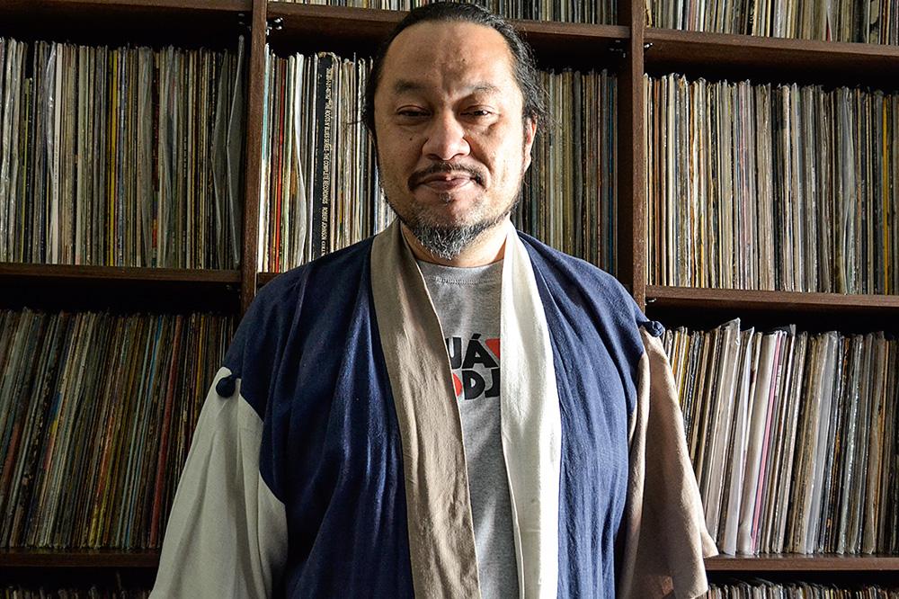 DJ Paulão em frente a uma estante de discos de vinil