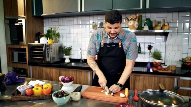Homem de avental culinário cortando uma cebola sobre tábua de madeira dentro de uma cozinha