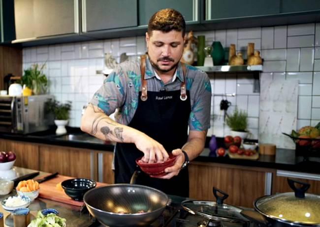 Homem com avental culinário jogando ingredientes de uma cumbuca para uma frigideira funda numa cozinha