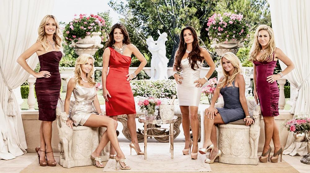 Seis mulheres brancas e bem trajadas posam em um jardim super ornamentado