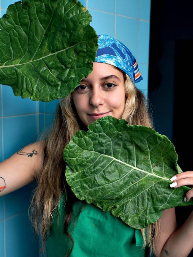 mulher segurando folhas de couve nas mãos próximas ao rosto