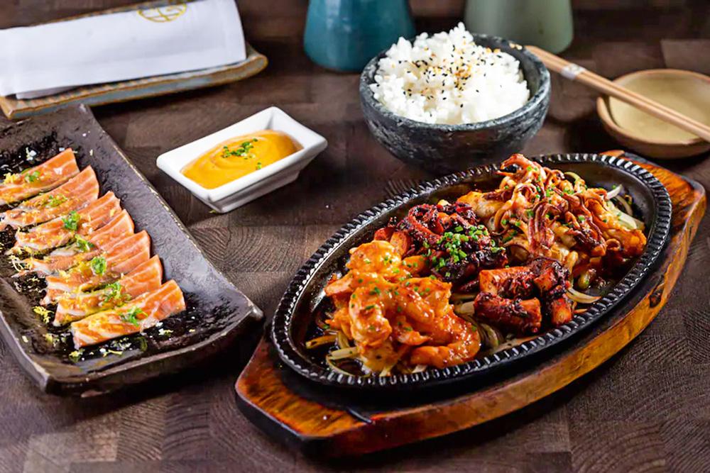 Prato de lula, camarão e polvo marinados em saquê aparecem em destaque na imagem. Ao lado aparece fatias de salmão trufado e arroz branco