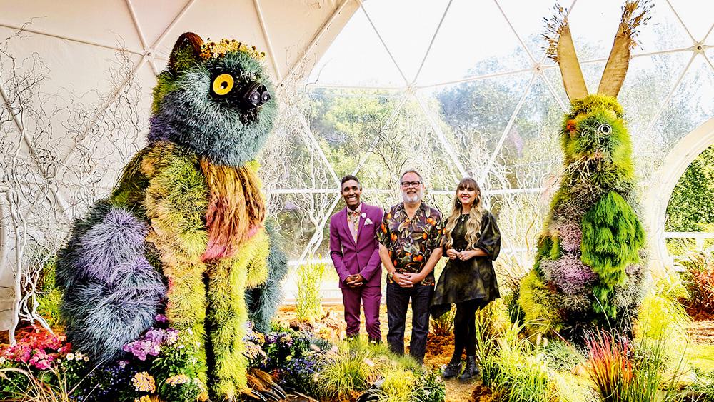 Dois homens e uma mulher bem arrumados posam em um jardim super ornamentado, com flores e plantas gigantes