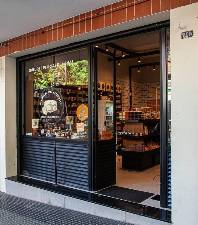 Fachada da loja A Casa do Queijo. Porta à direita com vitrine preta.