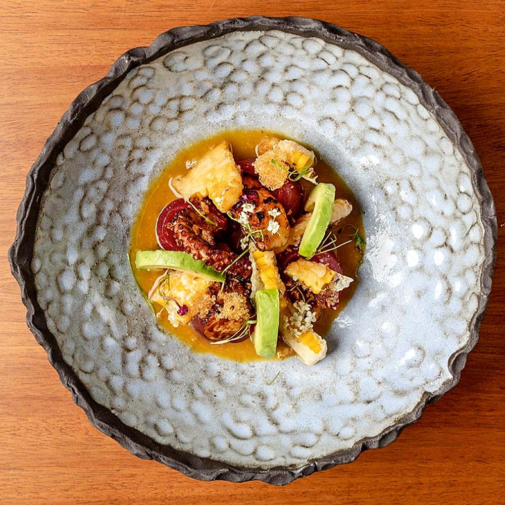 Prato redondo com polvo, atum, abacate e tempurá de milho.