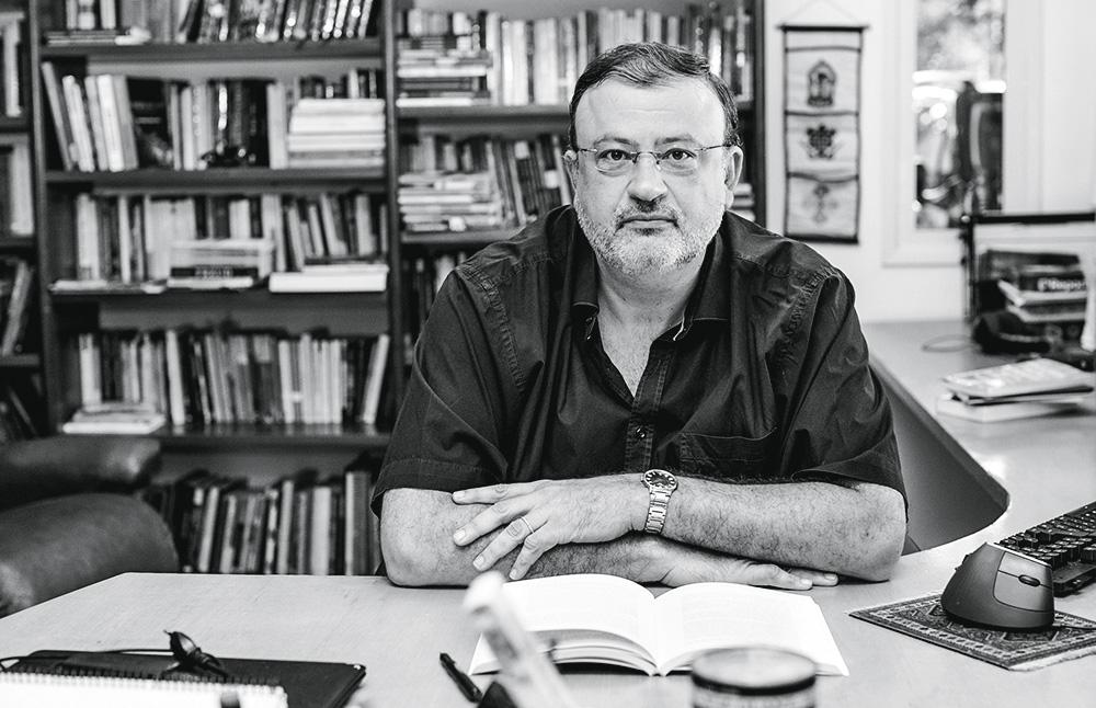 O psicanalista Christian Dunker posa em frente a uma estante de livros sentado em uma cadeira, com mesa na sua frente, que tem um livro aberto. Foto em preto e branco