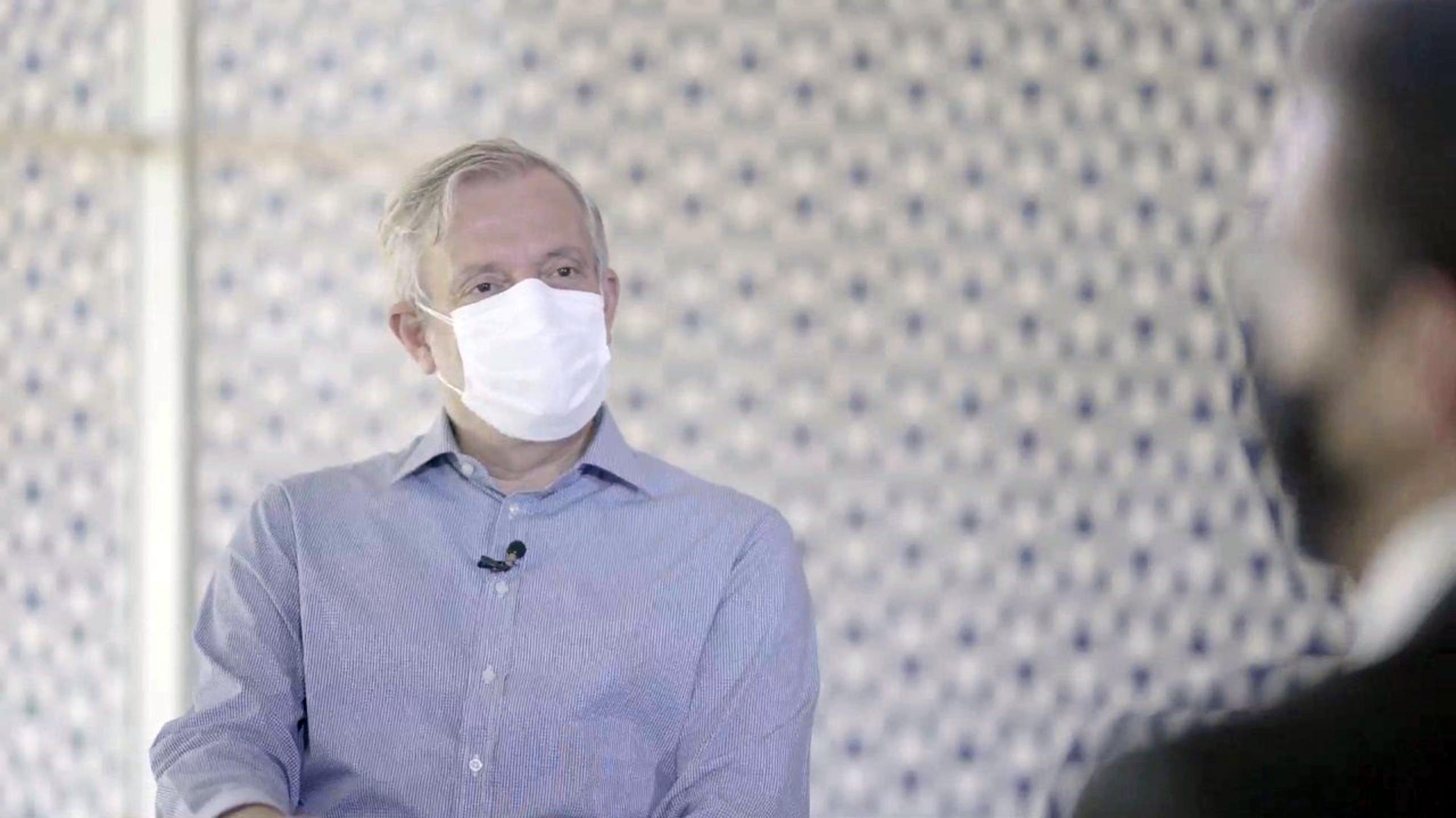 Repórter Álvaro Pereira Jr. aparece com máscara branca e camisa azul em frente a silhueta de Gustavo Mendes, gerente-geral de medicamentos da Anvisa.