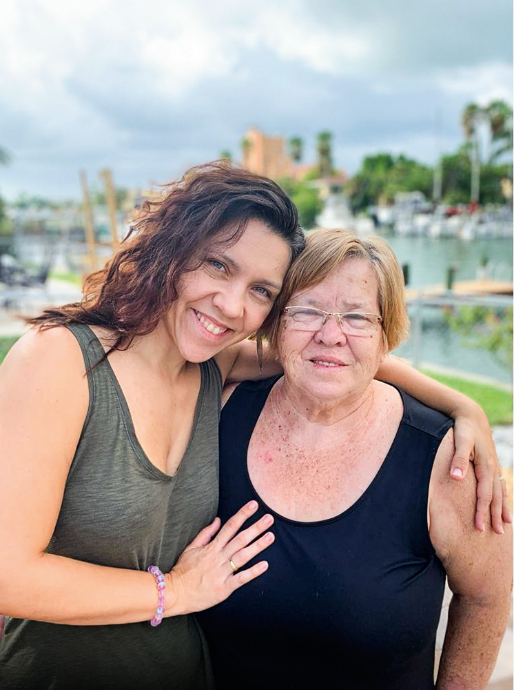 Ana Paula abraçando sua mãe com o braço esquerdo e ambas estão sorrindo