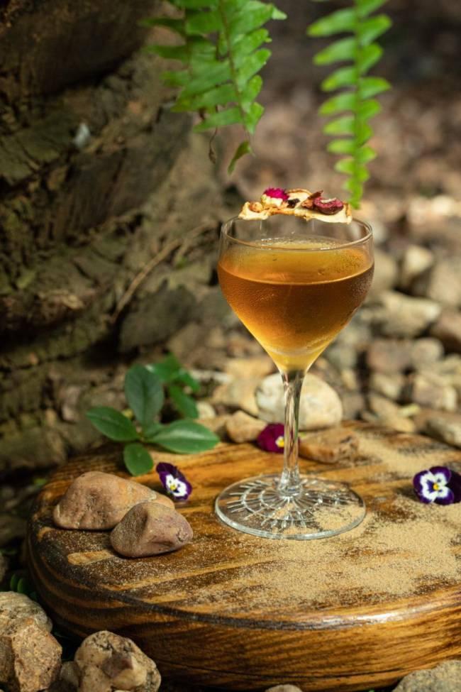 Taça de vidro com drink de coloração caramelo e biscoito na borda sobre tábua de madeira polvilhada com canela e adornada com flores roxas e pedrinhas. Ao fundo, ambiente com pedras e casca de árvore à esquerda.